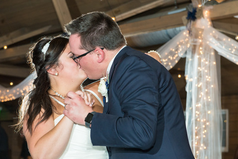 bride and groom kiss during the first dance in barn wedding venue